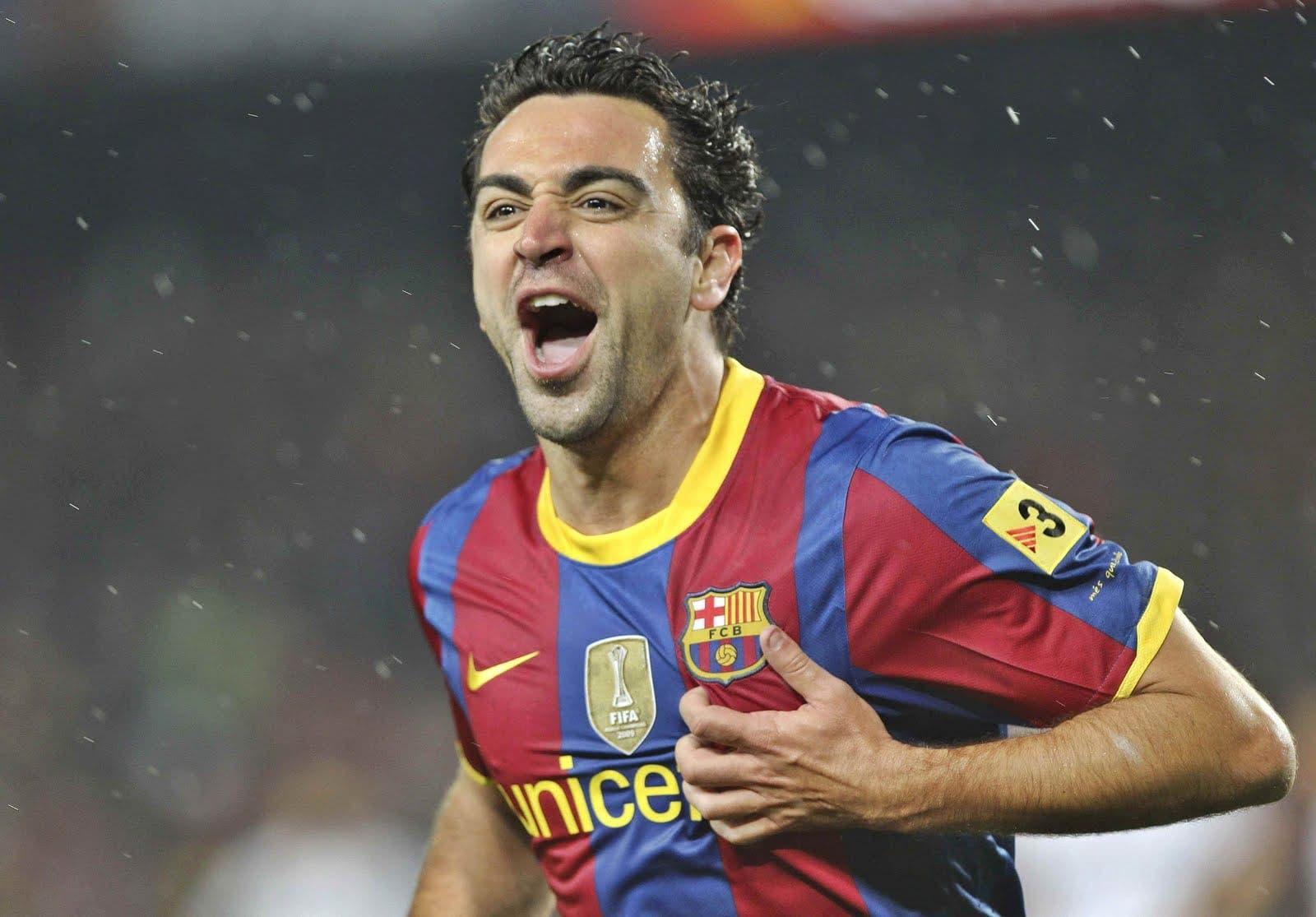 Xavi se toca el escudo celebrando un gol